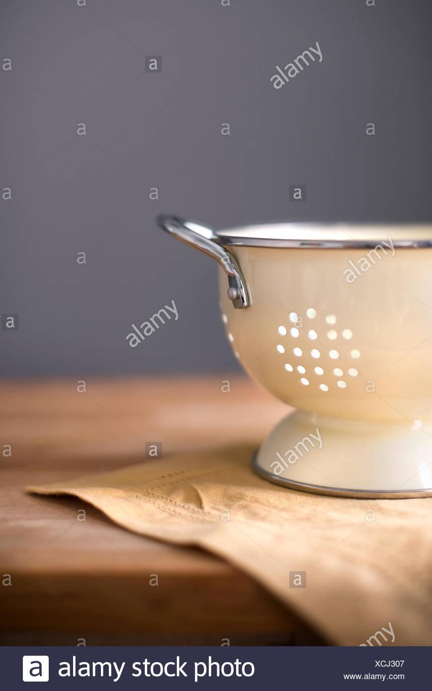 Pequeño tamiz en color crema con un contador de bloque de carnicero ropa de mostaza. Imagen De Stock