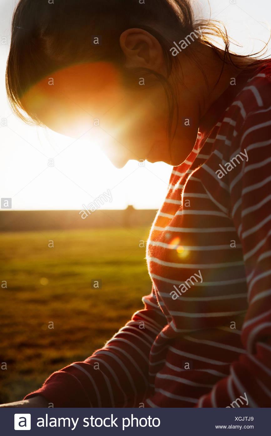 Sudáfrica, iluminada desde atrás mitad mujer adulta mirando hacia abajo Imagen De Stock