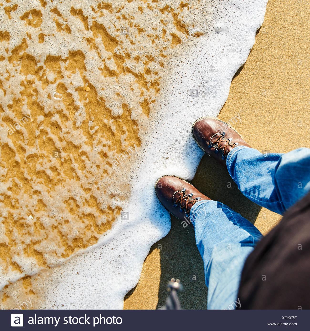 Bajo la sección del hombre zapatos en la orilla en la playa Imagen De Stock