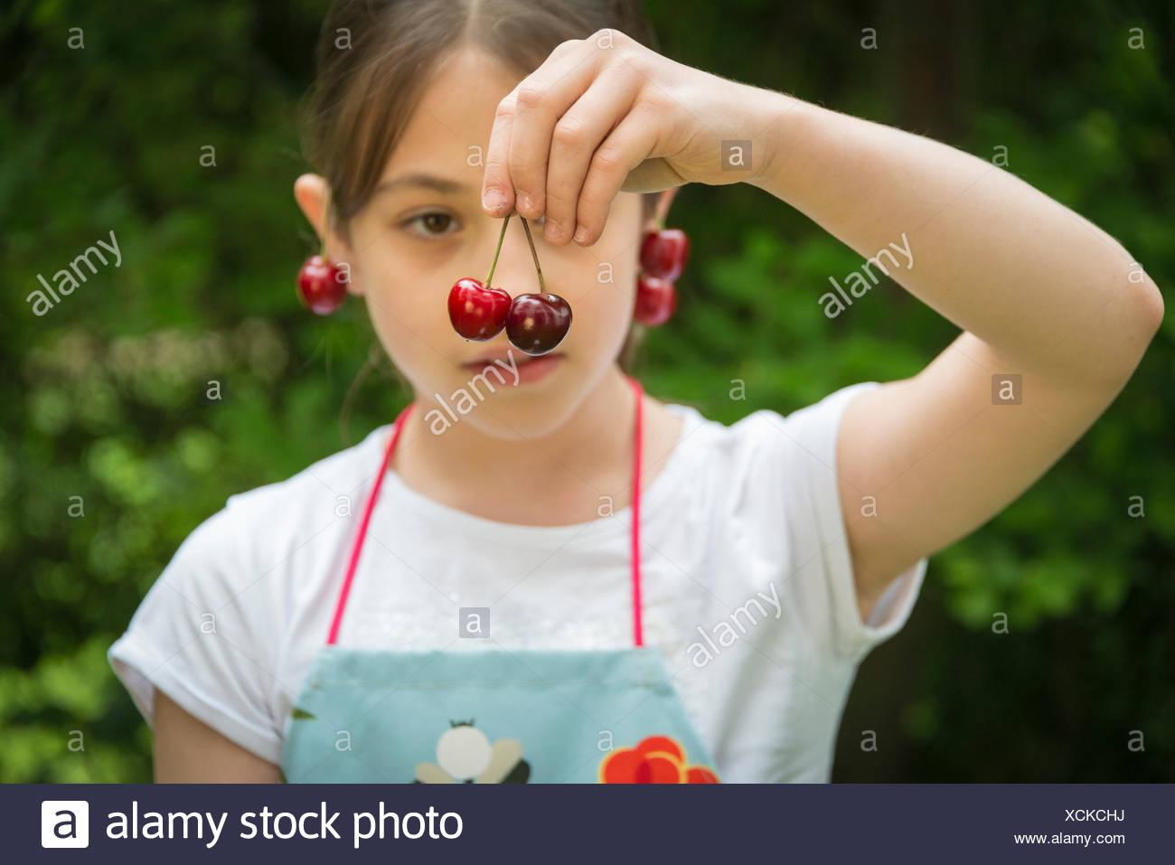 Chica con cerezas colgando de las orejas. Imagen De Stock
