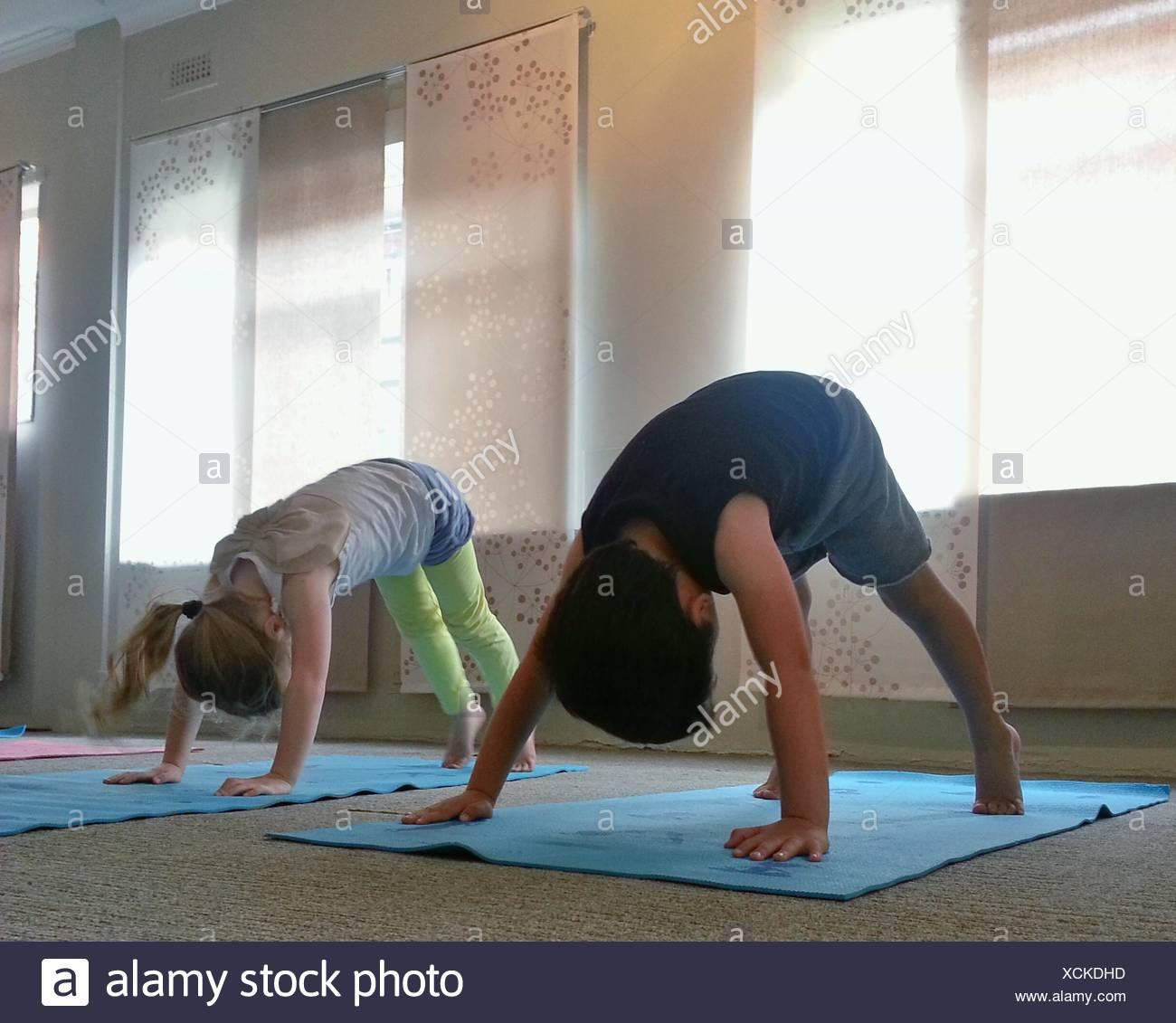 Dos niños haciendo perro boca abajo pose de yoga Imagen De Stock