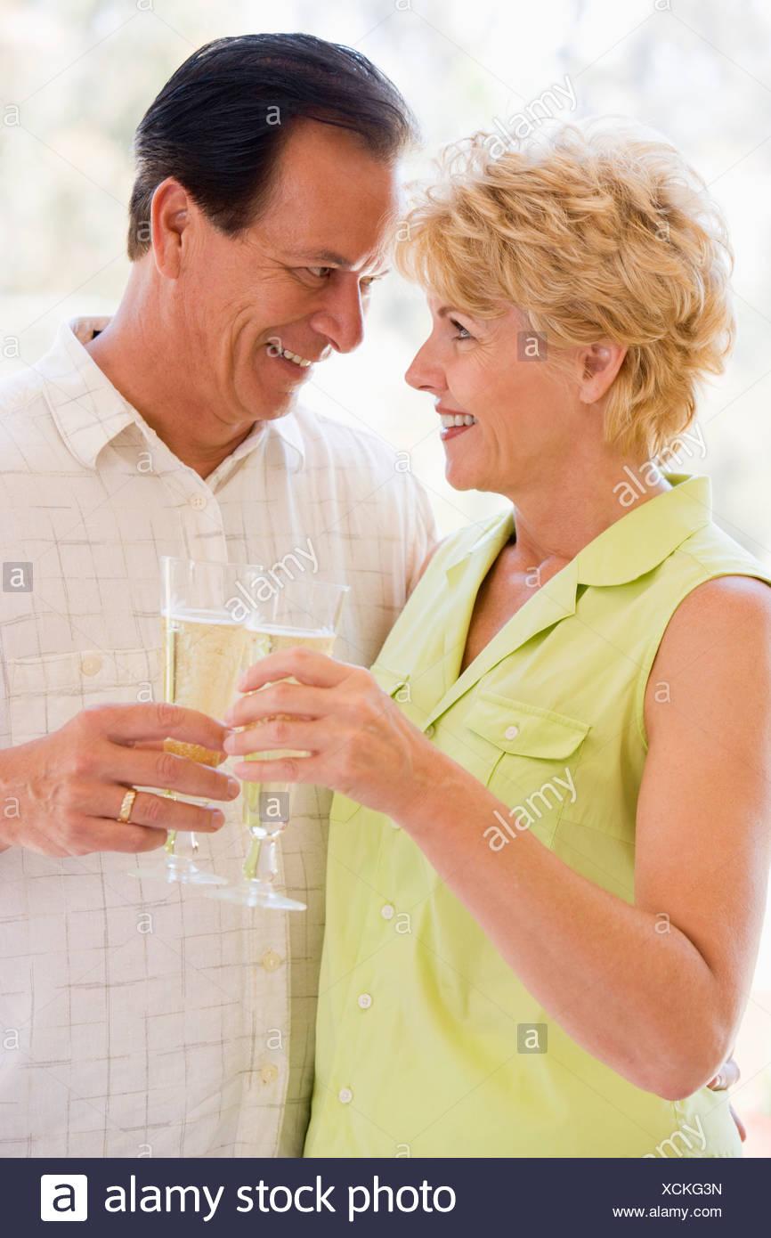Pareja sonriente y champán de tostado Imagen De Stock