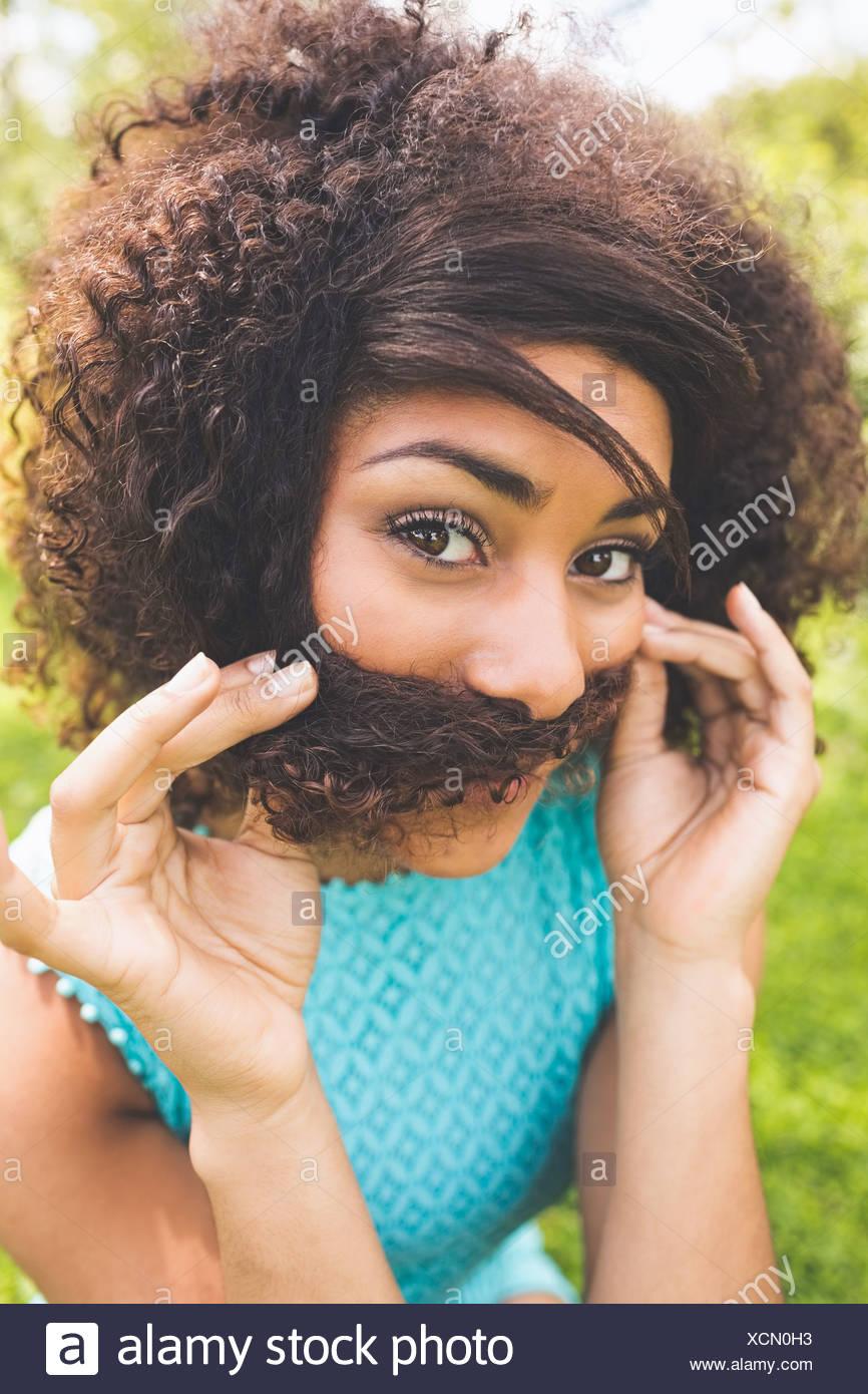 Hermosa morena feliz fingir que tiene un bigote Imagen De Stock