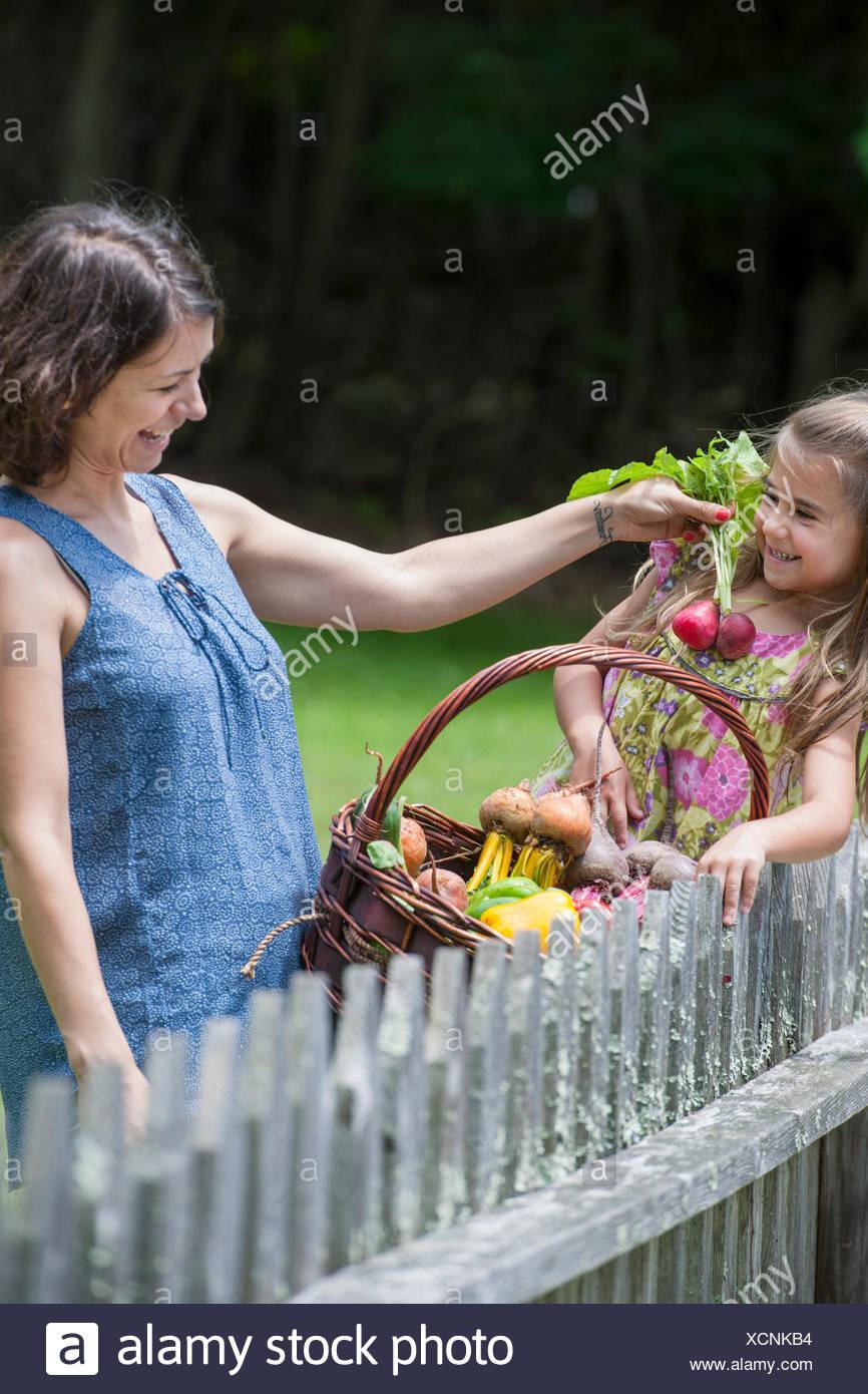 Madre e hija de pie en un jardín con una cesta de verduras. Imagen De Stock