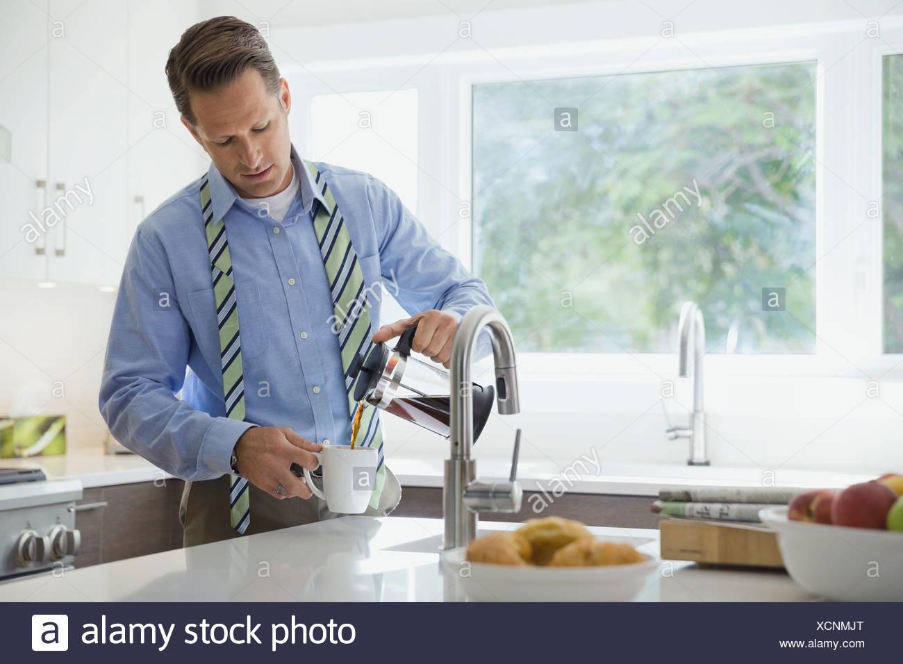 Empresario verter el café en la cocina doméstica Imagen De Stock