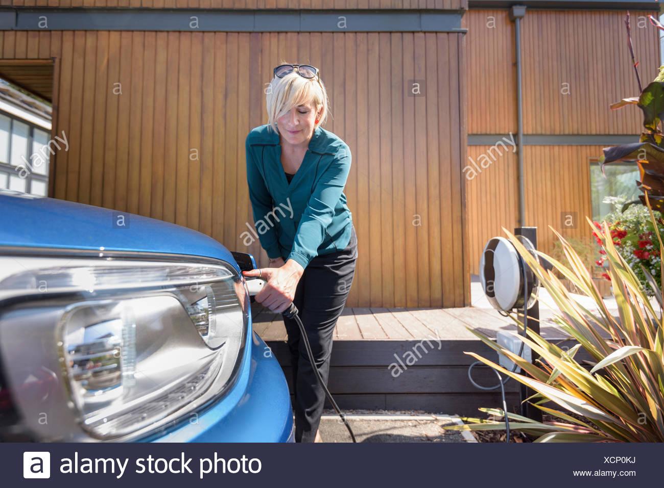 Mujer cargando un coche eléctrico desde el punto de carga Imagen De Stock