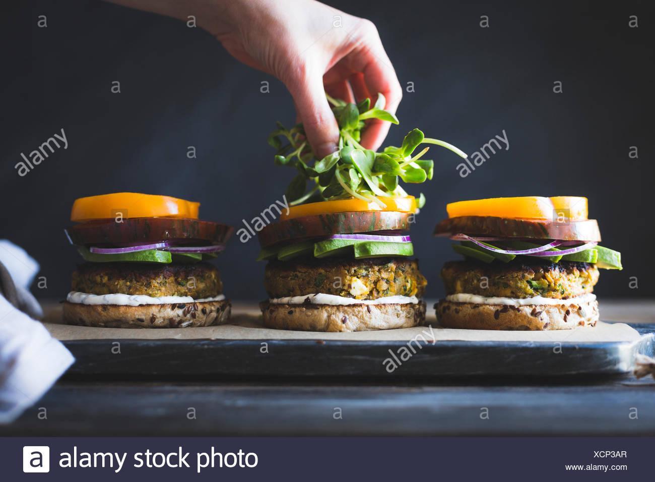 Aderezado el calabacín, el queso Feta y hamburguesas vegetarianas de garbanzo acuñadas con salsa de yogur Imagen De Stock