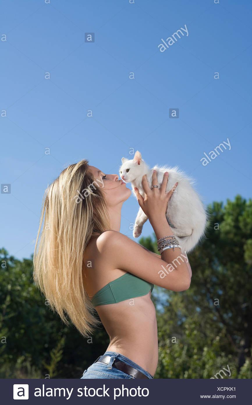 Jovencita besos gatito fuera Imagen De Stock