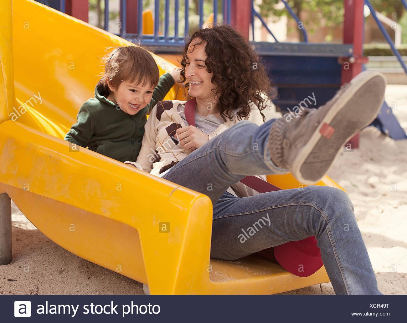 Madre e hijo en una diapositiva de playground Imagen De Stock