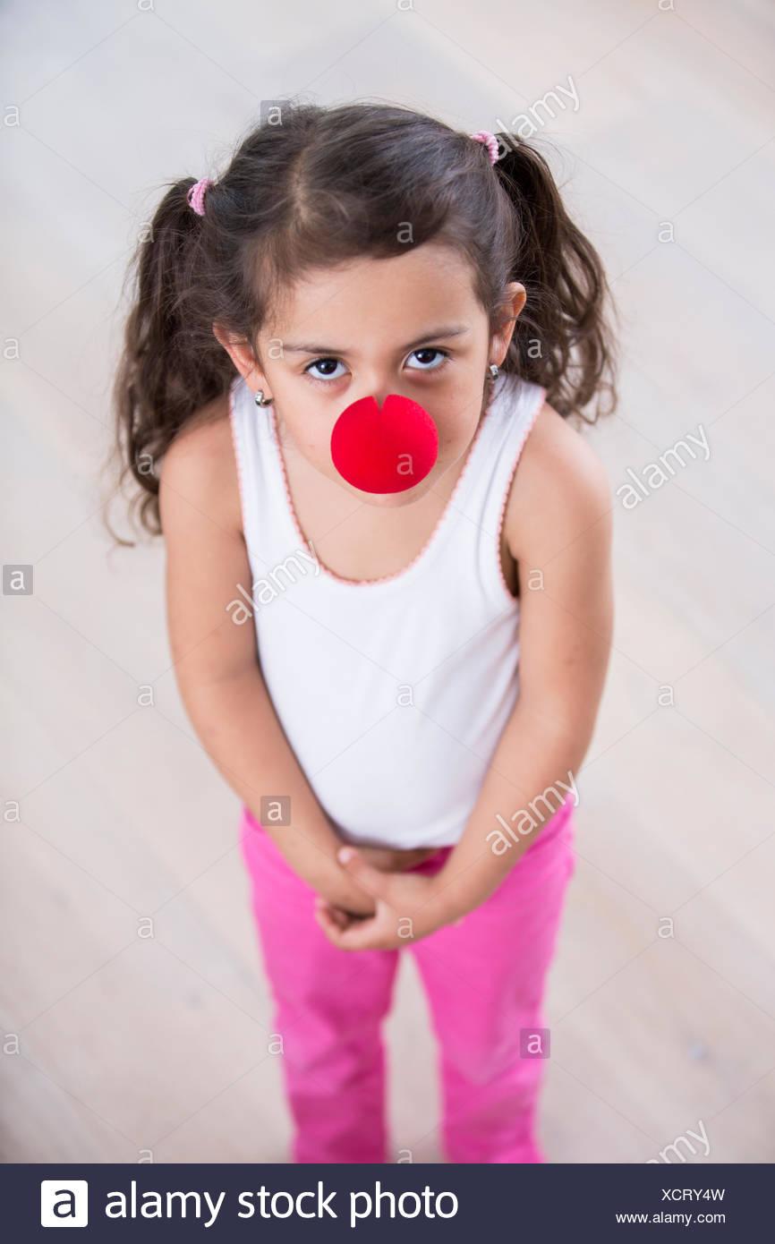 Retrato de cute little girl vistiendo la nariz de payaso en casa Imagen De Stock
