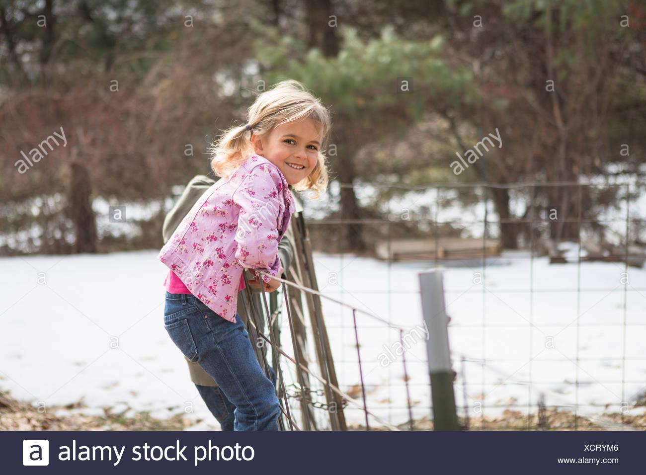 Joven escalando alambrada en el campo Foto de stock