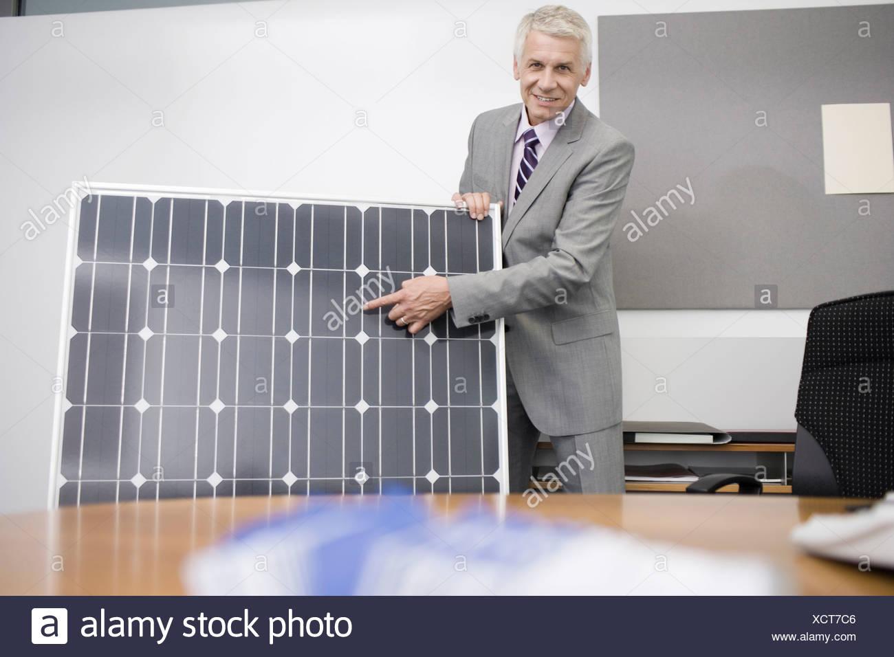 Un maduro hombre de negocios en una oficina demostrando un panel solar Imagen De Stock
