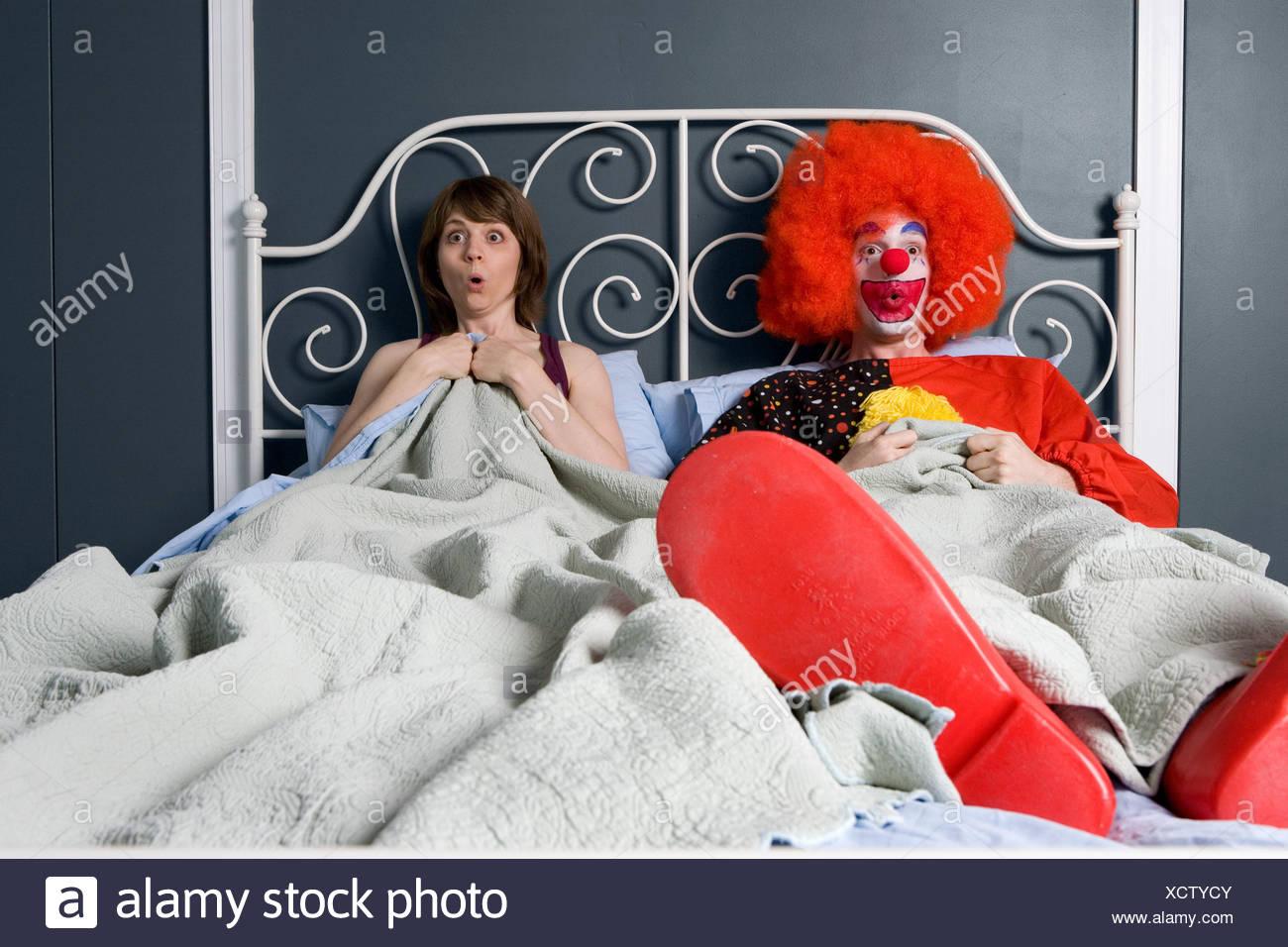 Payaso y mujer sorprendida al encontrarse en la cama juntos Imagen De Stock