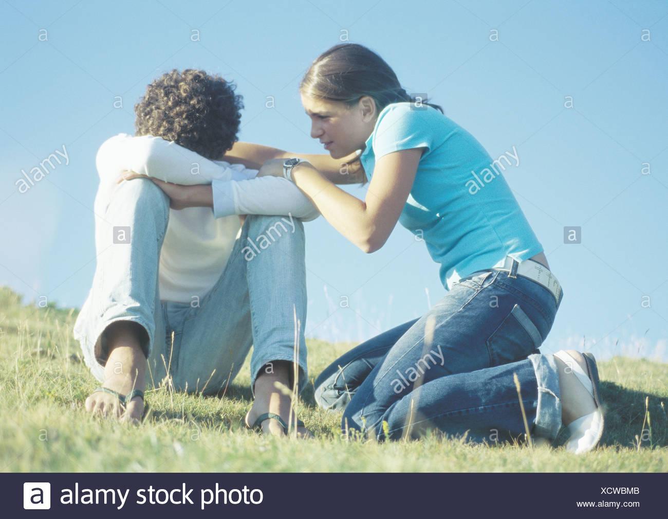La pareja de adolescentes, niña tratando de hablar con el niño con la cabeza hacia abajo Foto de stock