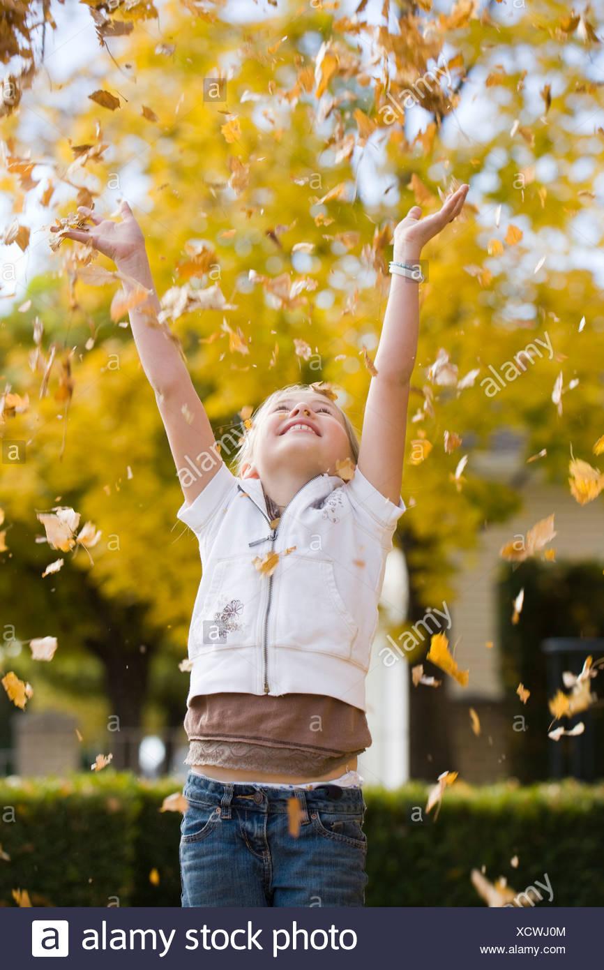 Niña jugando en hojas caídas. Foto de stock