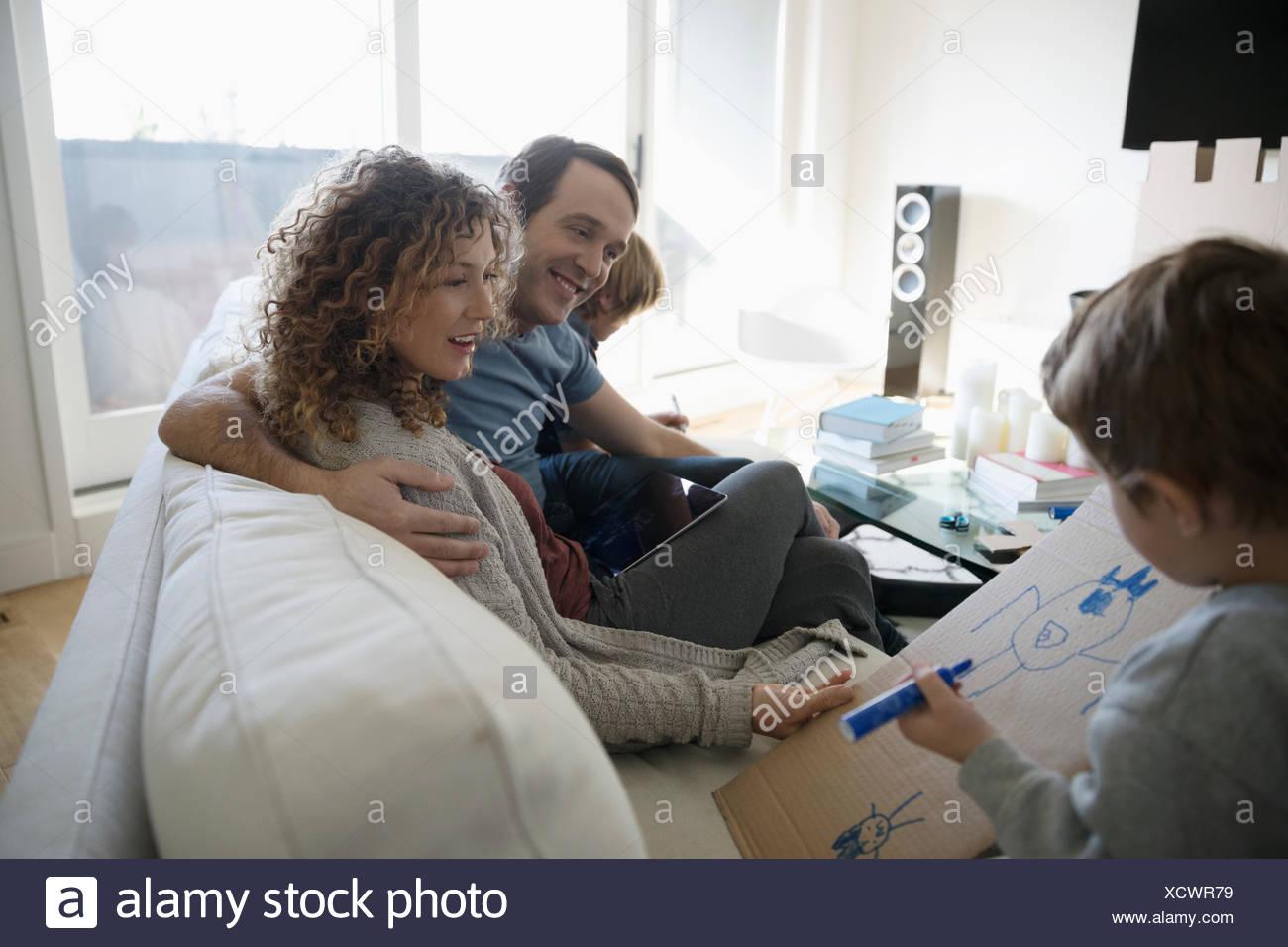 Sofá relax en familia,hijo de padres mostrando el dibujo sobre cartón Imagen De Stock