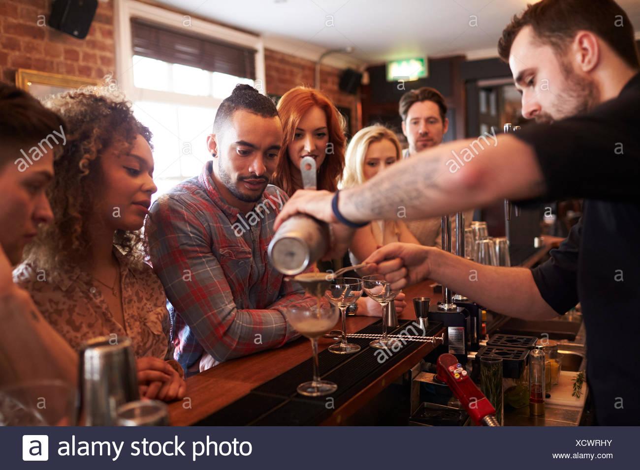 Cantinero dando lecciones de preparación de cócteles a los amigos en el bar Imagen De Stock