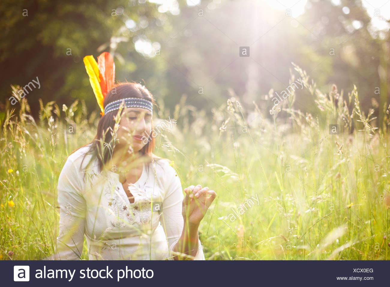 Mujer madura en Native American tocado en pasto largo Imagen De Stock