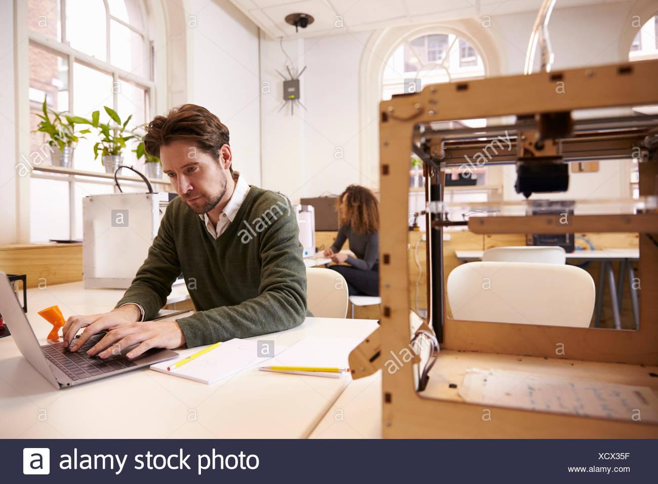 Diseñador que trabaja con impresoras 3D y software de CAD en Studio Imagen De Stock