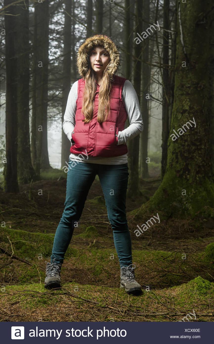 Una joven mujer de pie en un bosque con su capucha y las manos en sus bolsillos. Imagen De Stock