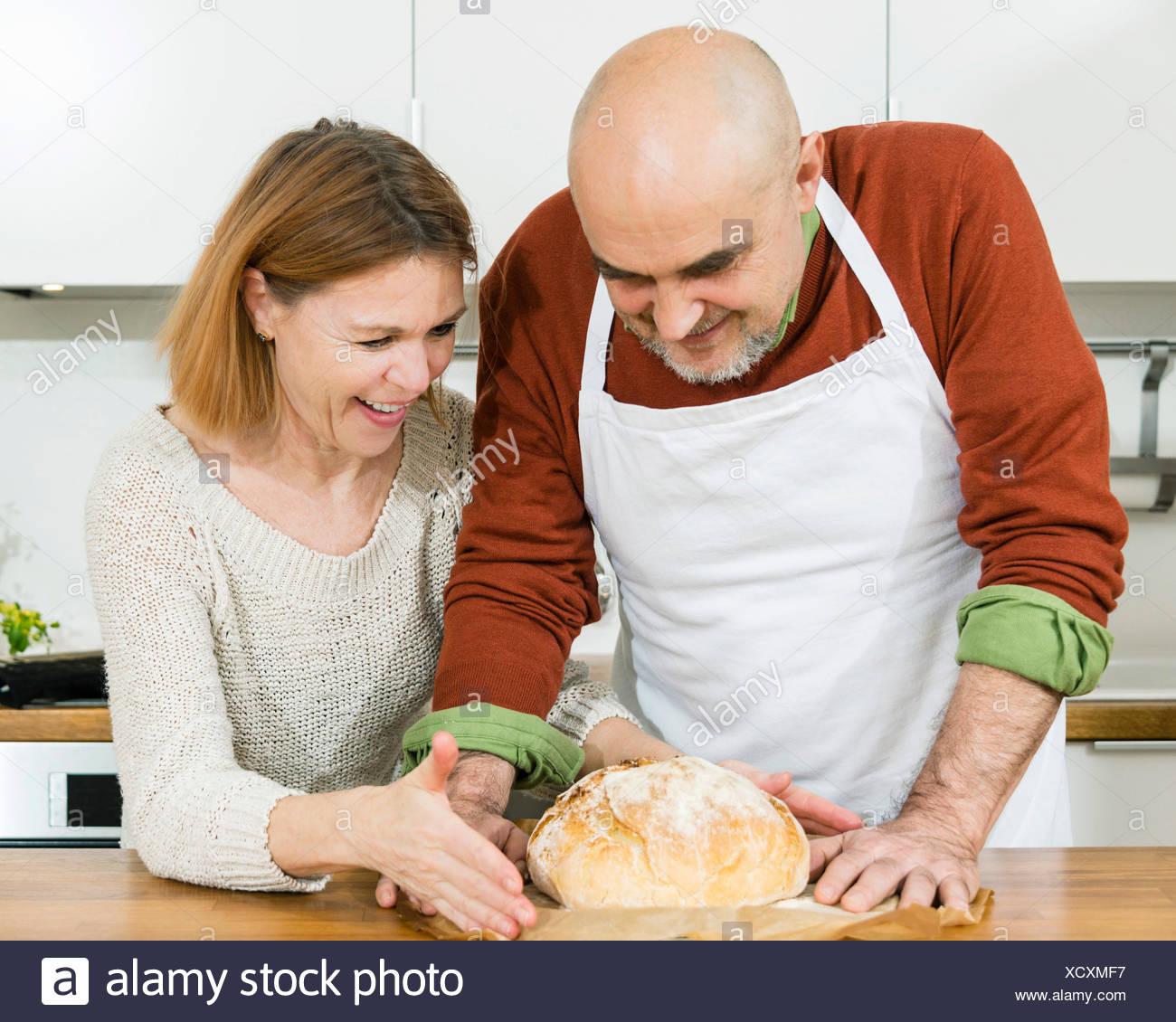 Las parejas ancianas en la cocina mirando pan fresco Imagen De Stock