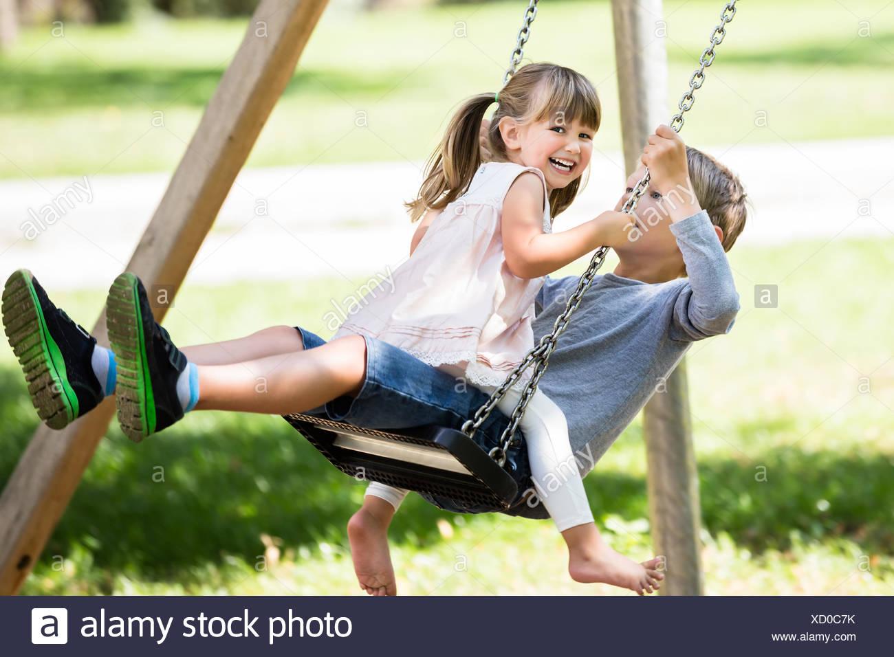 Hermano y hermana, disfrutando el columpio en el parque Imagen De Stock