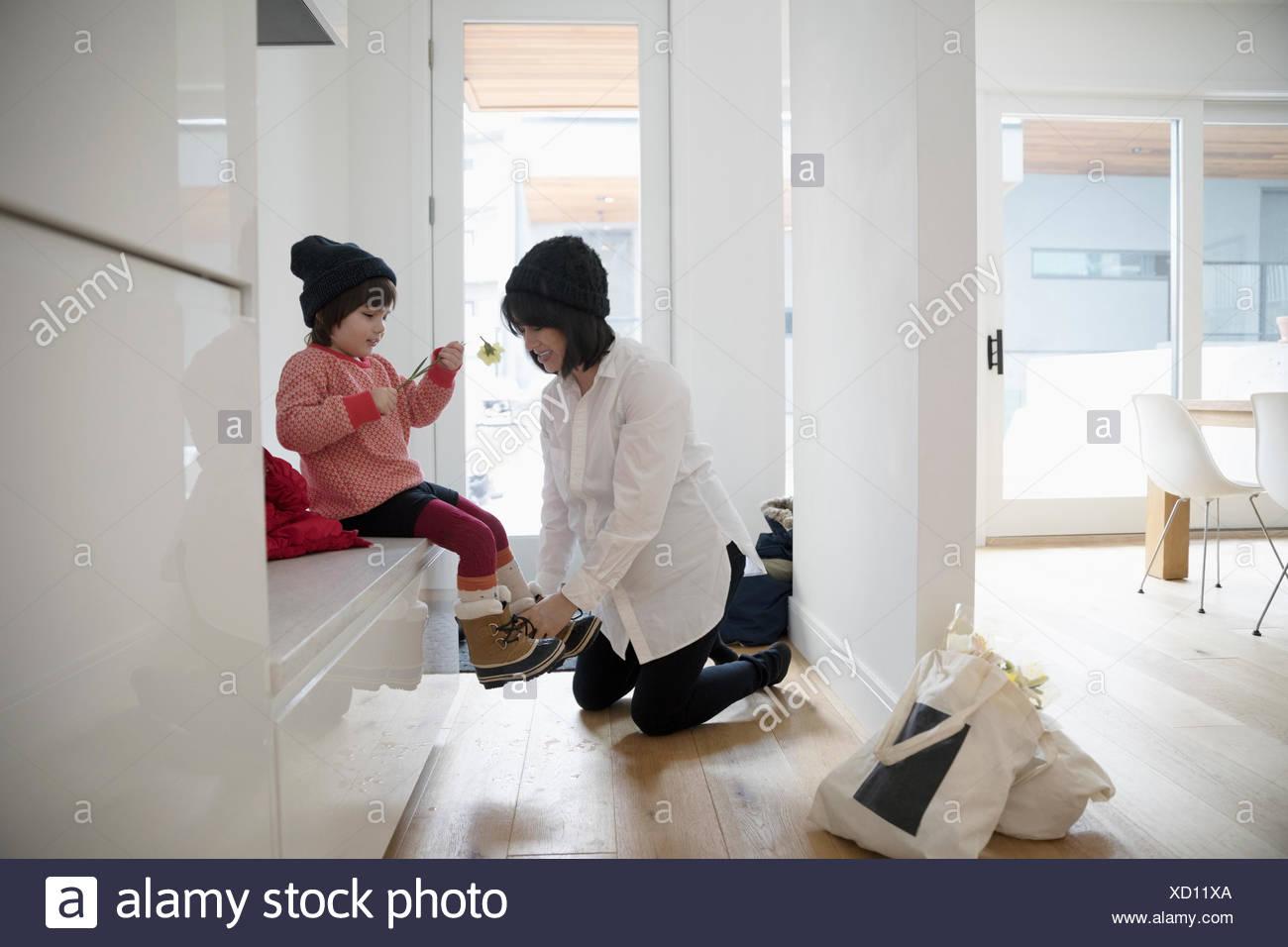 Madre embarazada poniendo las botas de niño hija Imagen De Stock