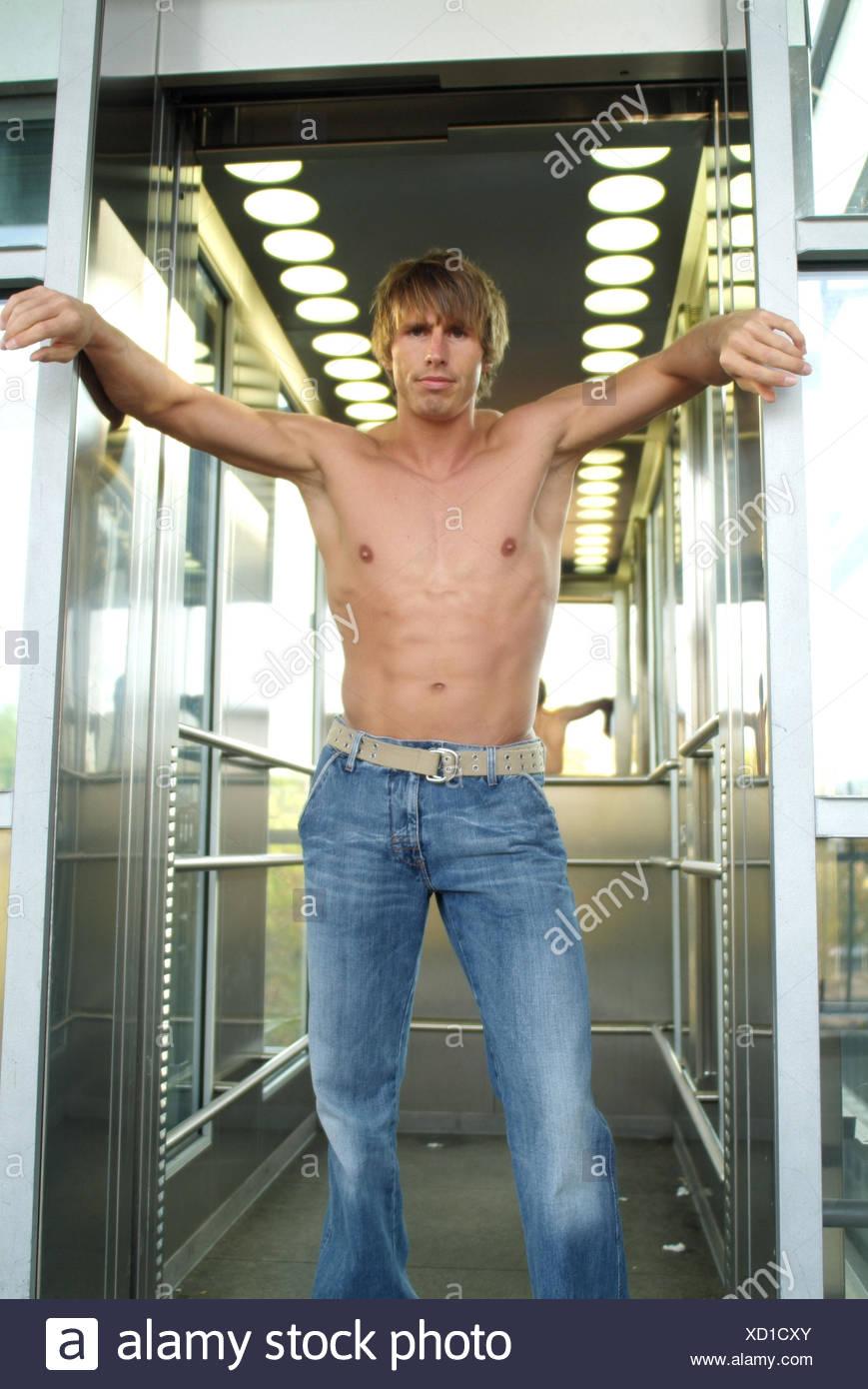 """Elevación, hombre, joven, libre en la parte superior del cuerpo, fresco, levante, levante, puerta abierta, levantar la puerta, abrió, machista, lady-killer, braggart, """"Sueños"""", modelo varonil, jeans, stand, magro, considere orgullosamente, descuidado, auto-confianza, decididamente, desafiante, órganos, w Imagen De Stock"""