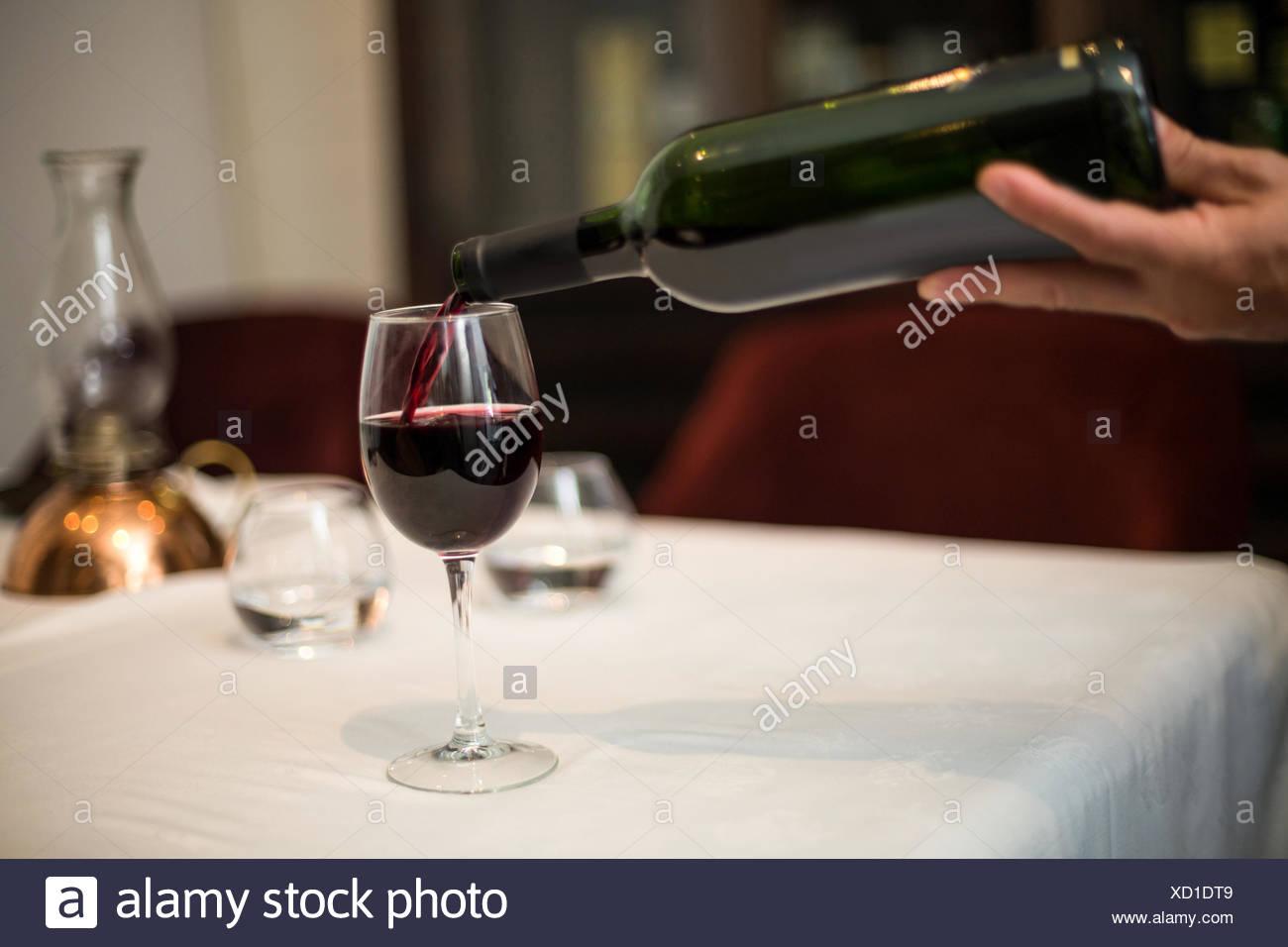 Camarero vertiendo un vaso de vino tinto Imagen De Stock