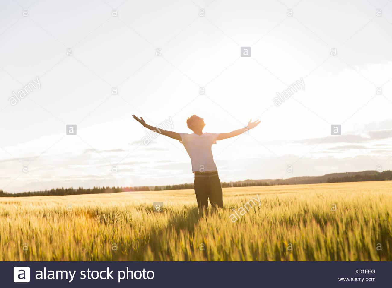 Hombre en un soleado día de campo con los brazos levantados Imagen De Stock