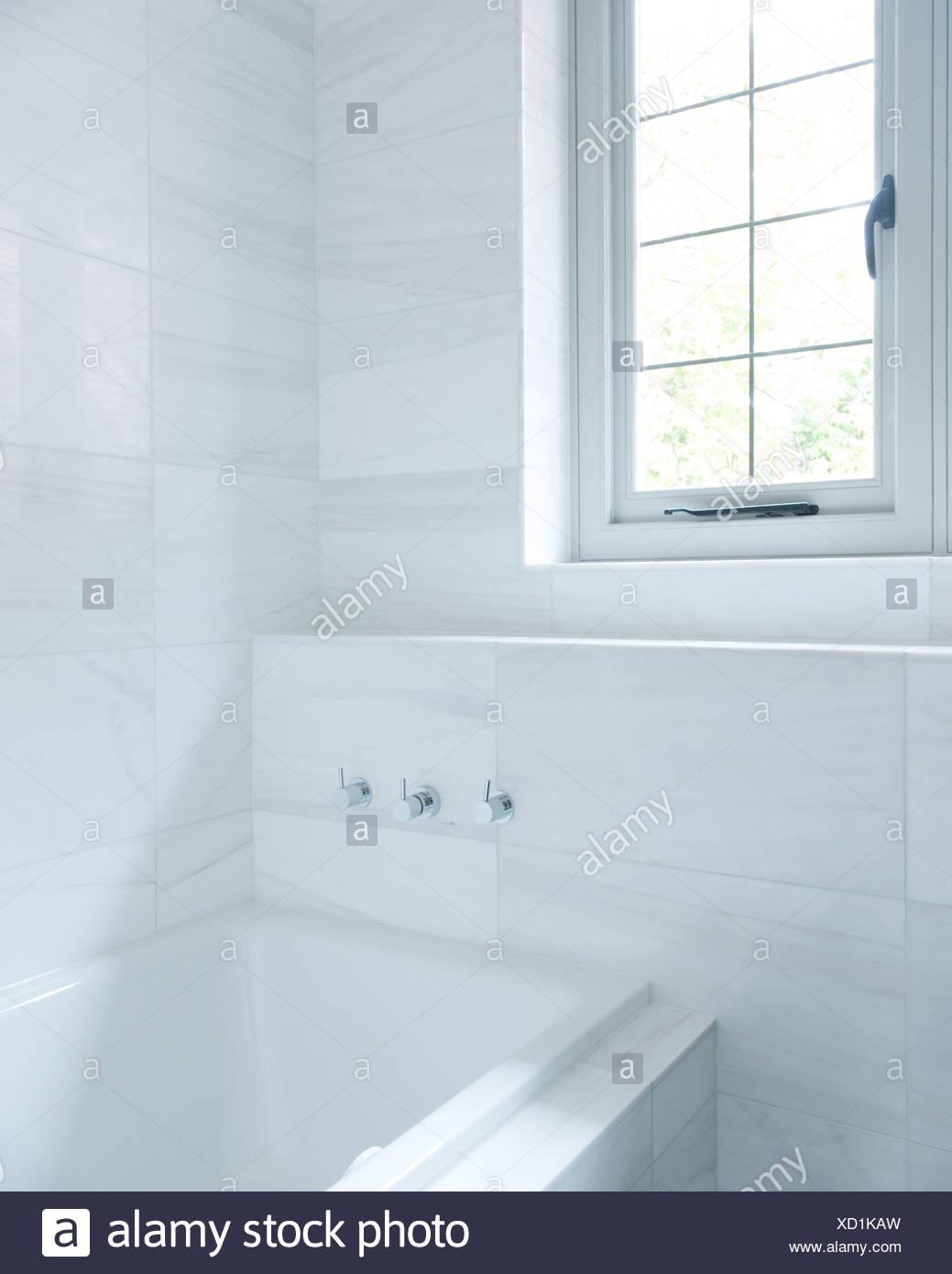 Un cuarto de baño con azulejos de mármol blanco Foto ...