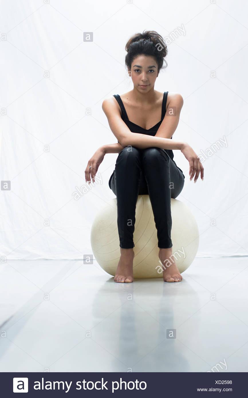 Retrato de estudio de seguro joven sentado en ejercicio de pelota Imagen De Stock