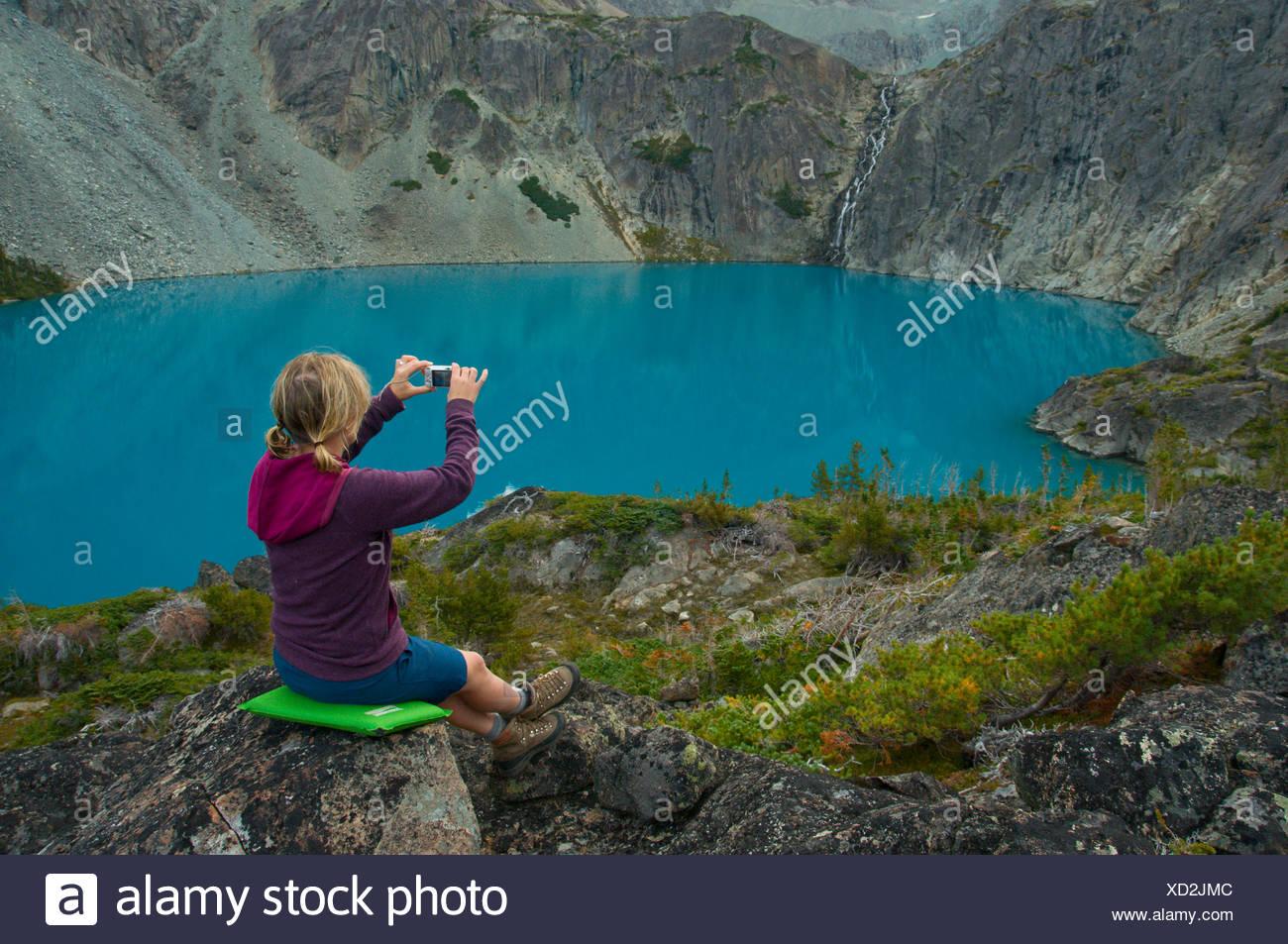 Una joven mujer ajusta una foto de una cascada y un lago azul con una cámara de apuntar y disparar, British Columbia, Canadá Imagen De Stock