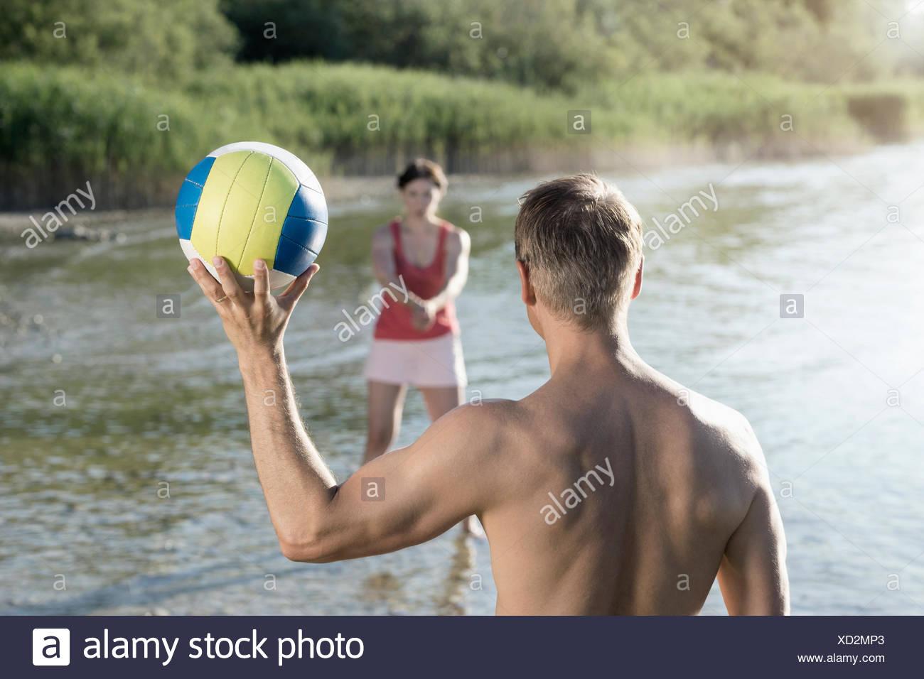 Pareja madura jugando voleibol en el lago, Baviera, Alemania Imagen De Stock