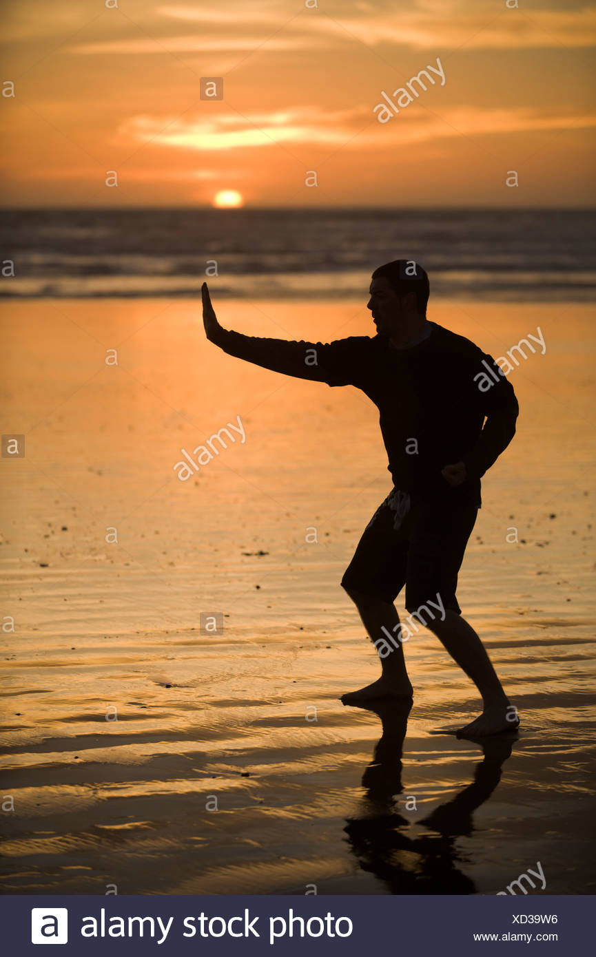 Un hombre adulto medio prácticas Taekwondo en la playa al anochecer en Morro Bay, California. Imagen De Stock