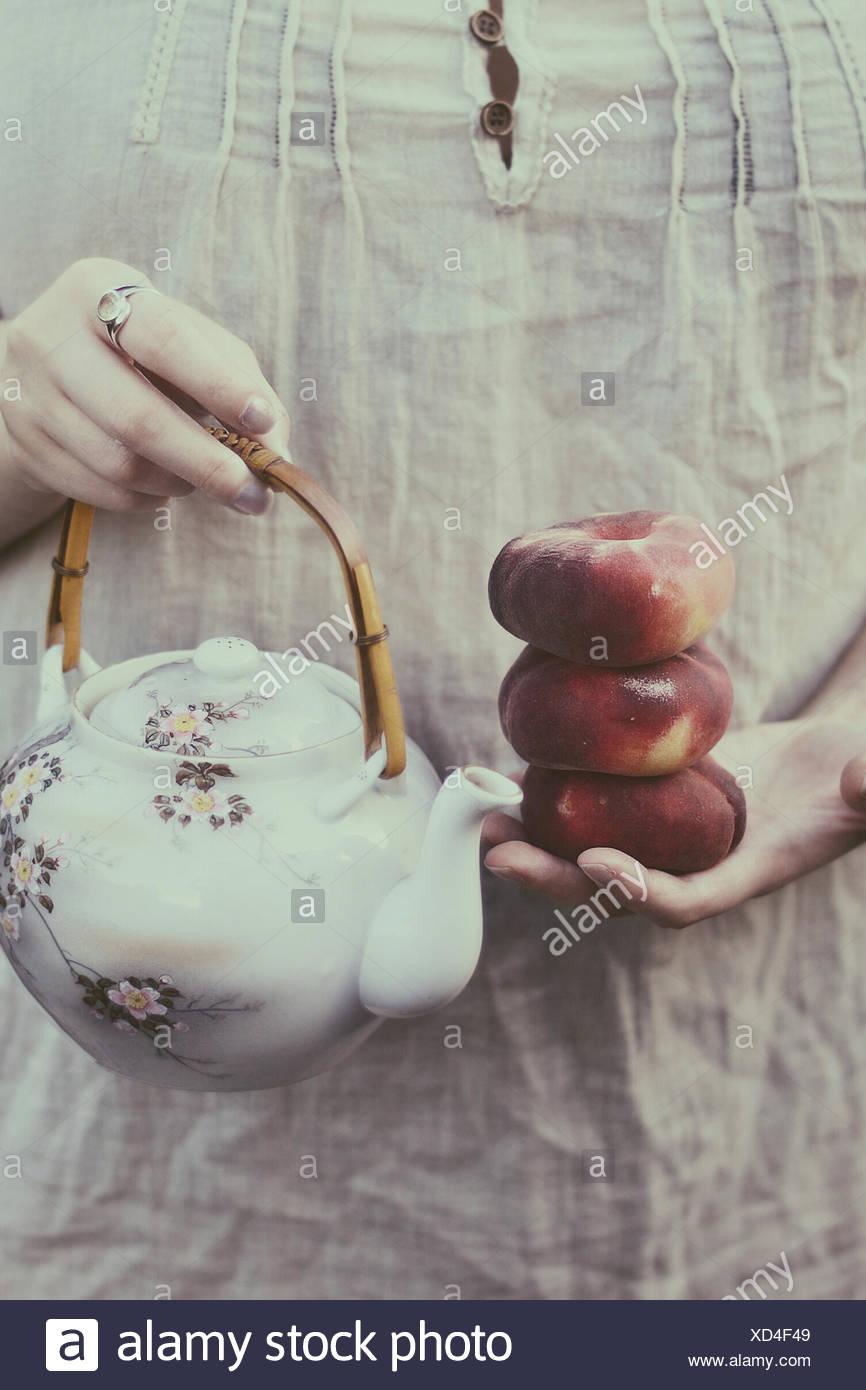 Reino Unido, Inglaterra, Warwickshire, Stratford-upon-Avon, Mujer sosteniendo los melocotones y té oriental pot Imagen De Stock
