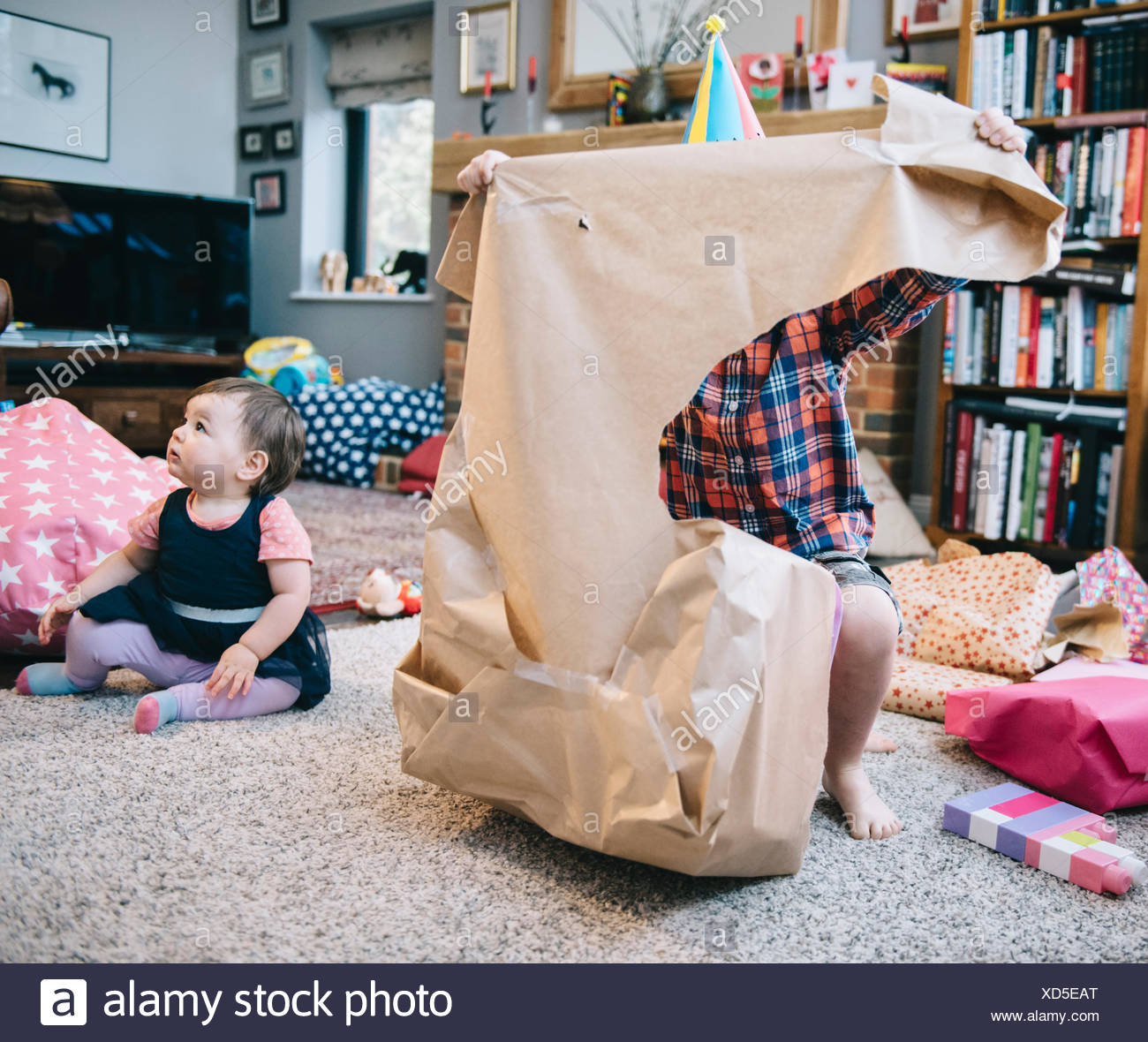 Un niño desenvolver se presenta en una fiesta de cumpleaños. Imagen De Stock
