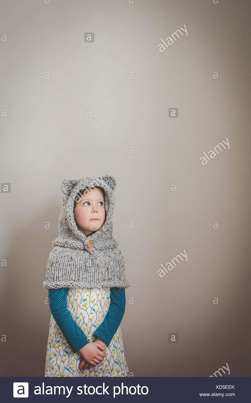 Retrato de una chica que llevaba un salpicadero tejida con orejas de oso mirando hacia arriba Imagen De Stock