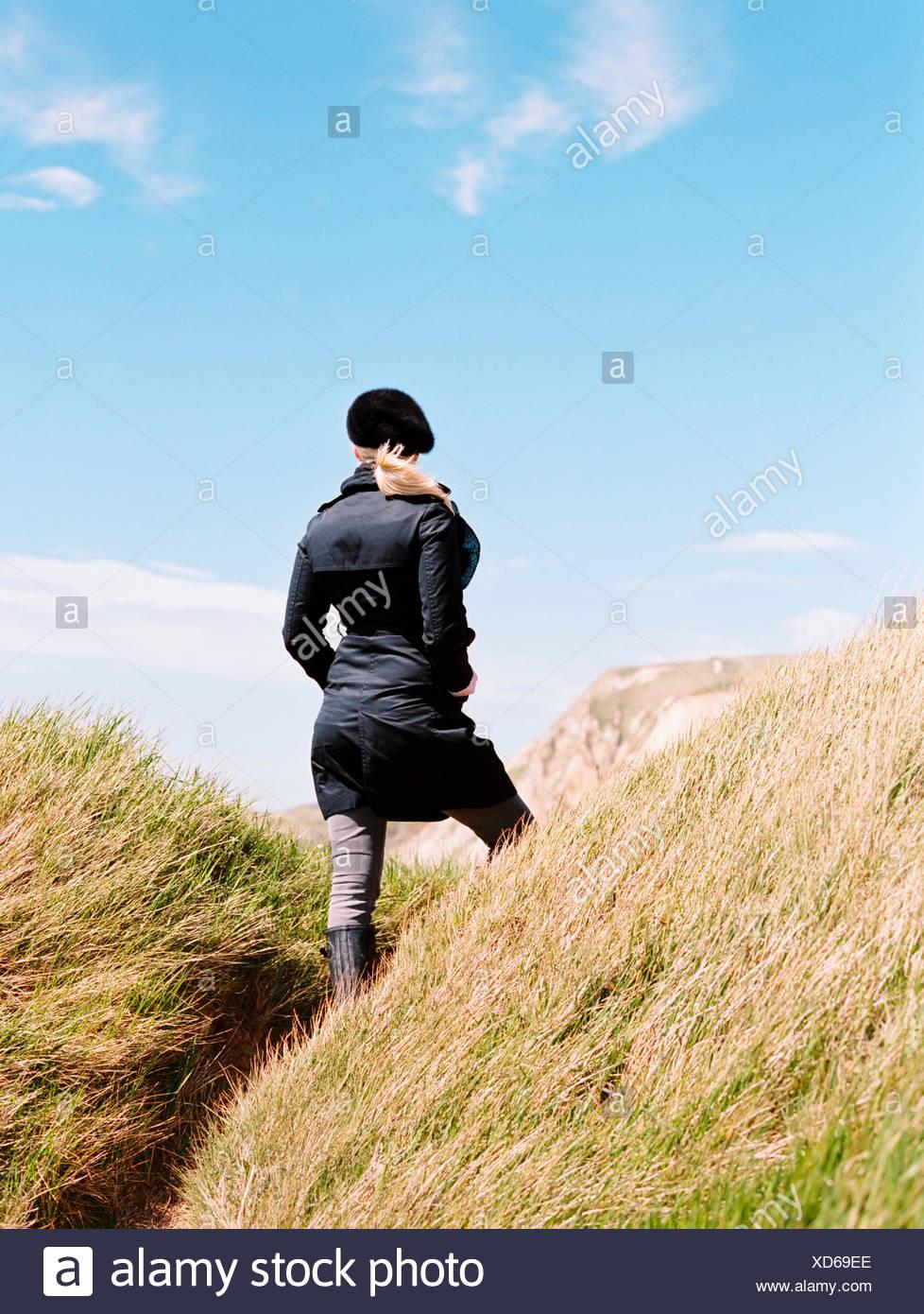 Una mujer en un abrigo y boina parado entre las dunas de arena de la costa 49b4dc2ea67
