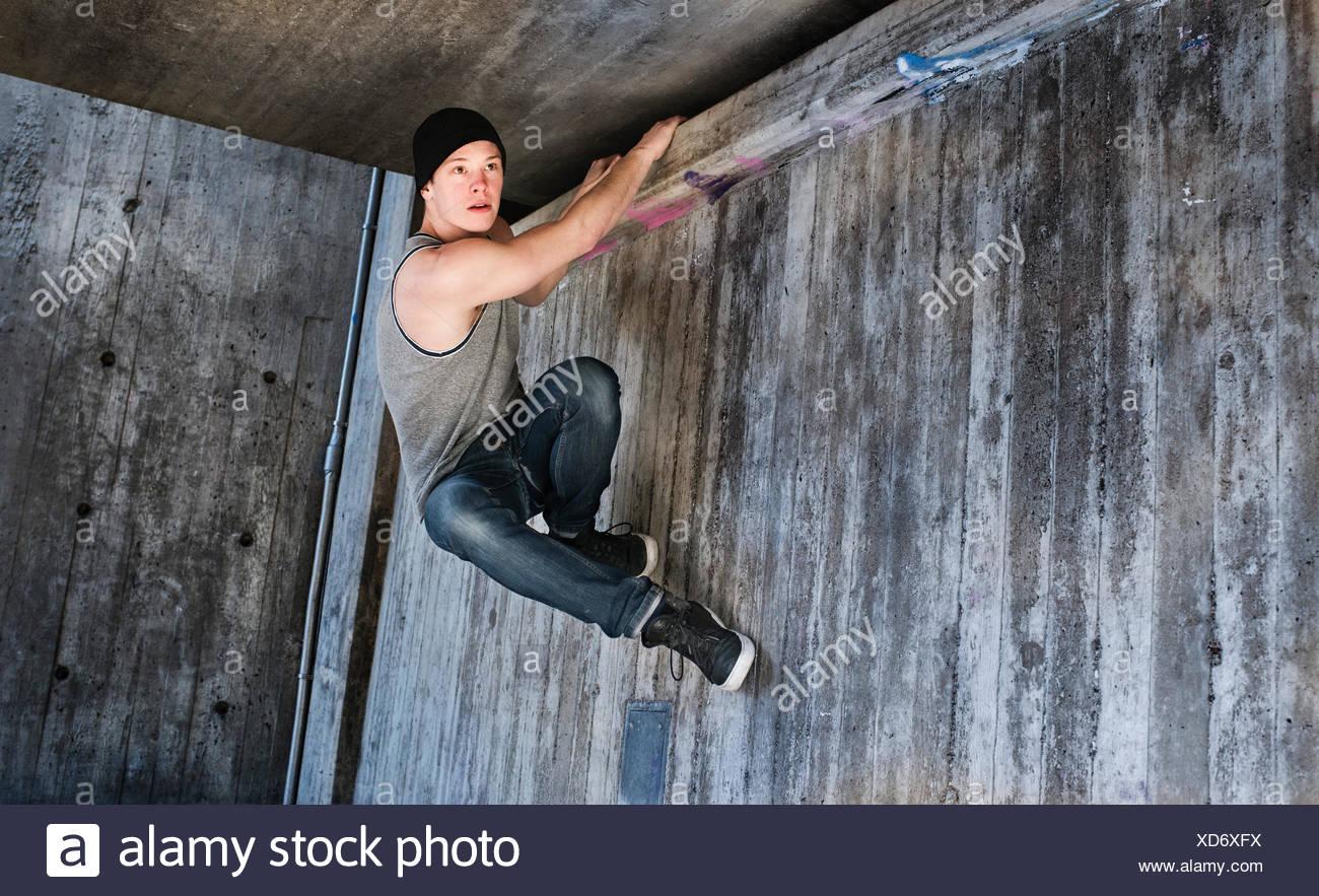 Joven colgando de un parkour mover en muro de hormigón, Suecia Imagen De Stock
