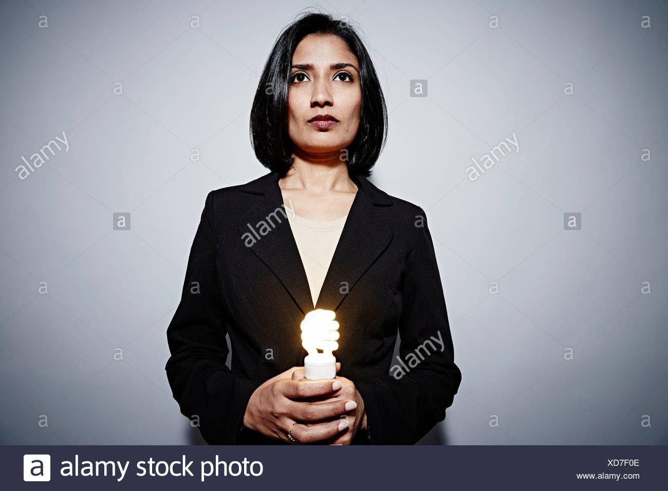 Retrato de estudio de la empresaria sosteniendo el ahorro de energía bombilla Imagen De Stock