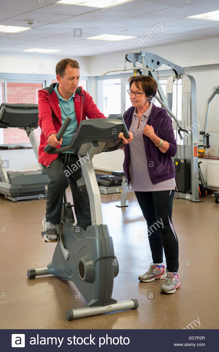 Formador ayudar a una mujer con el ciclo en un gimnasio Imagen De Stock