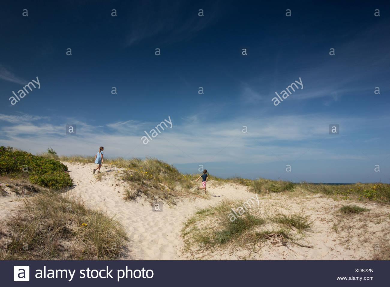 Hermano y hermana que se ejecuta a través de las dunas de arena Imagen De Stock