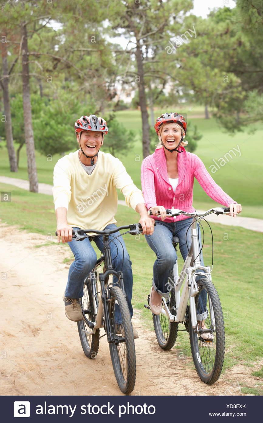 Una mujer joven montando en bicicleta en el parque Foto de stock