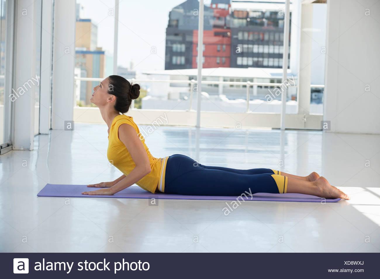 La mujer ejerce sobre la colchoneta de ejercicios en un gimnasio Imagen De Stock