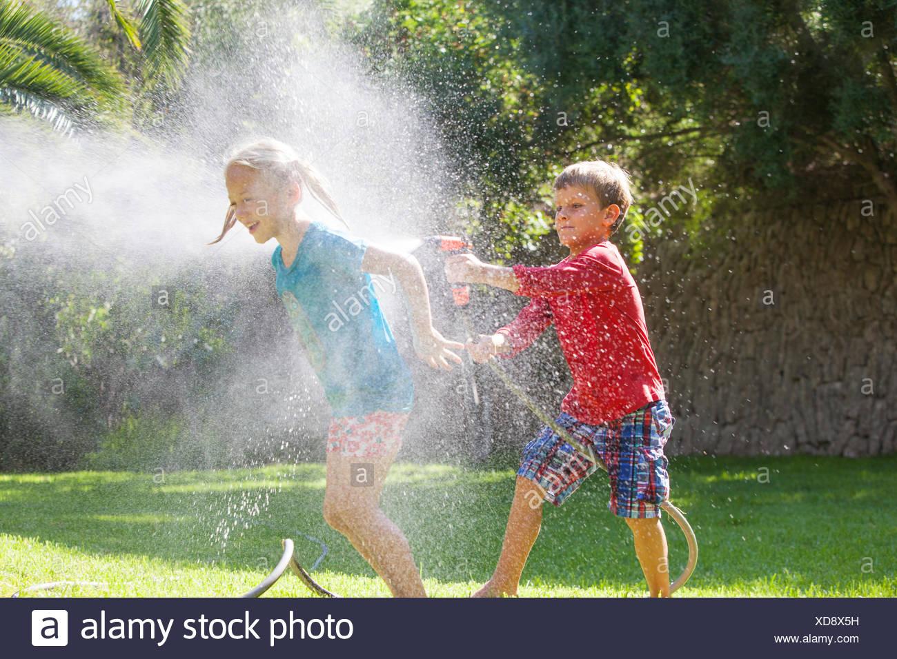 Chico Chica salpicaduras en jardín con rociadores de agua Imagen De Stock