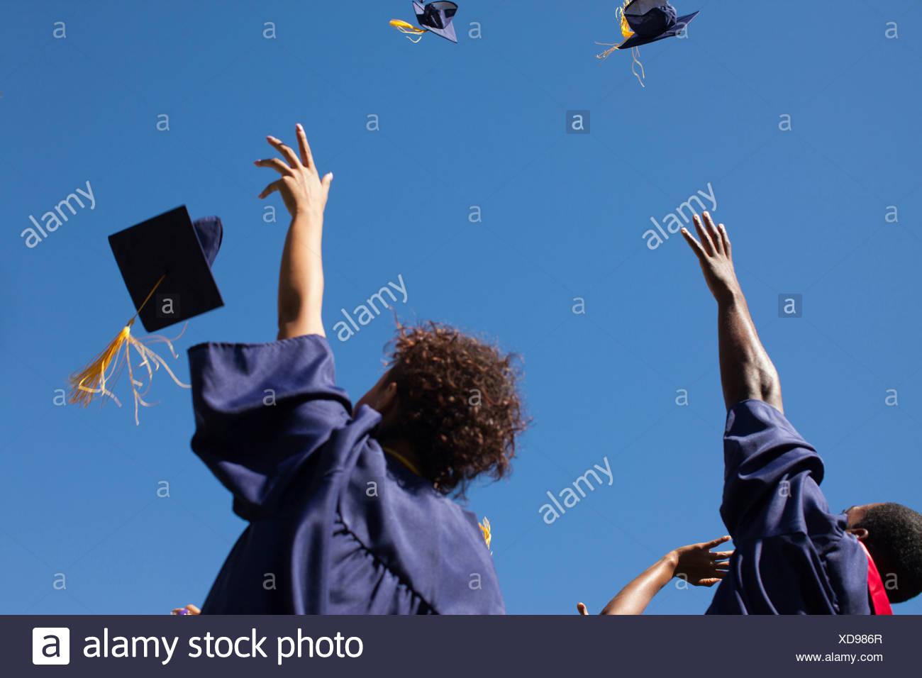Graduados arrojando las tapas en el aire al aire libre Imagen De Stock