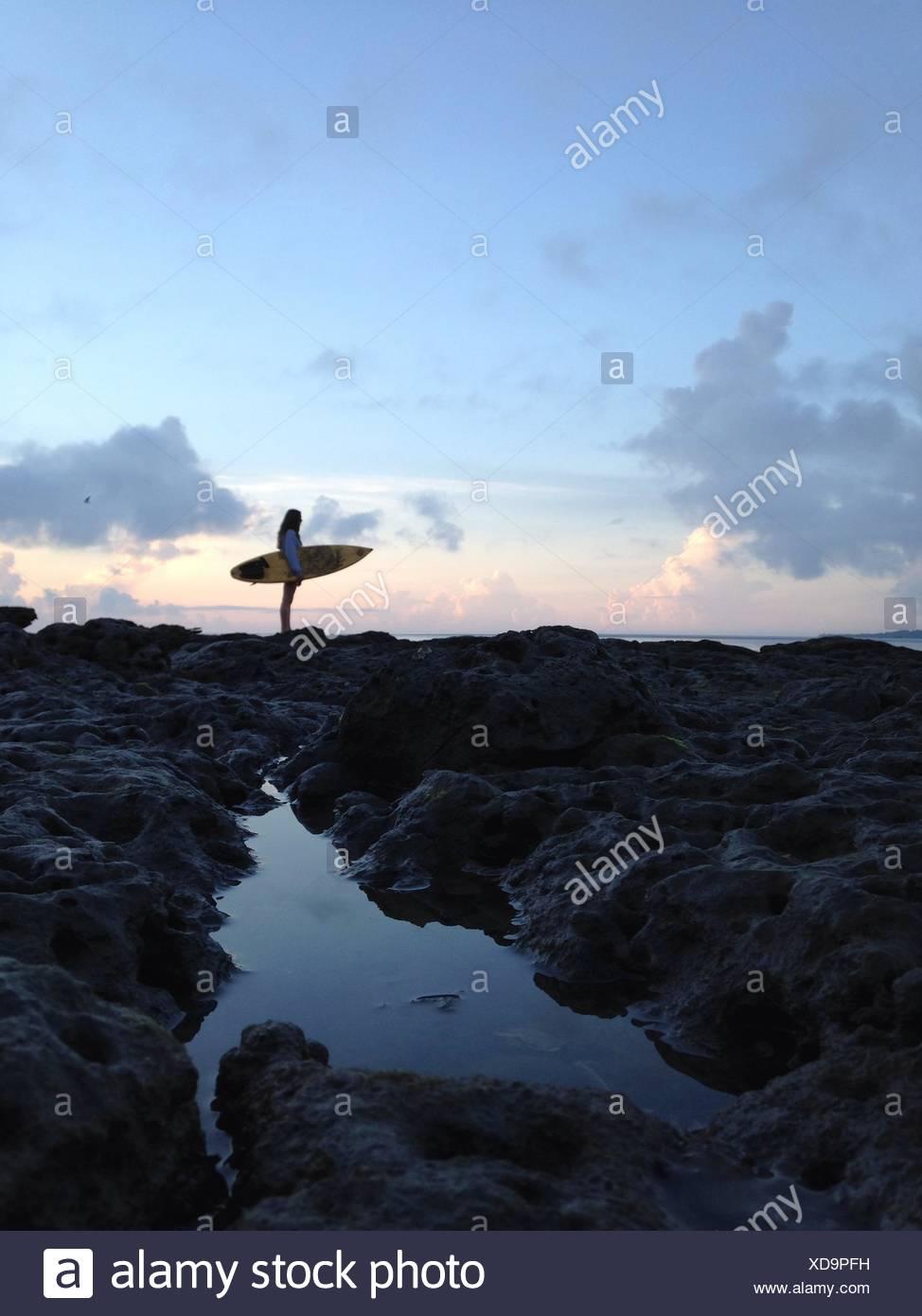Estados Unidos, la Florida, el condado de Duval, Jacksonville Beach, vista lateral de la mujer sosteniendo las tablas de surf en la playa Imagen De Stock