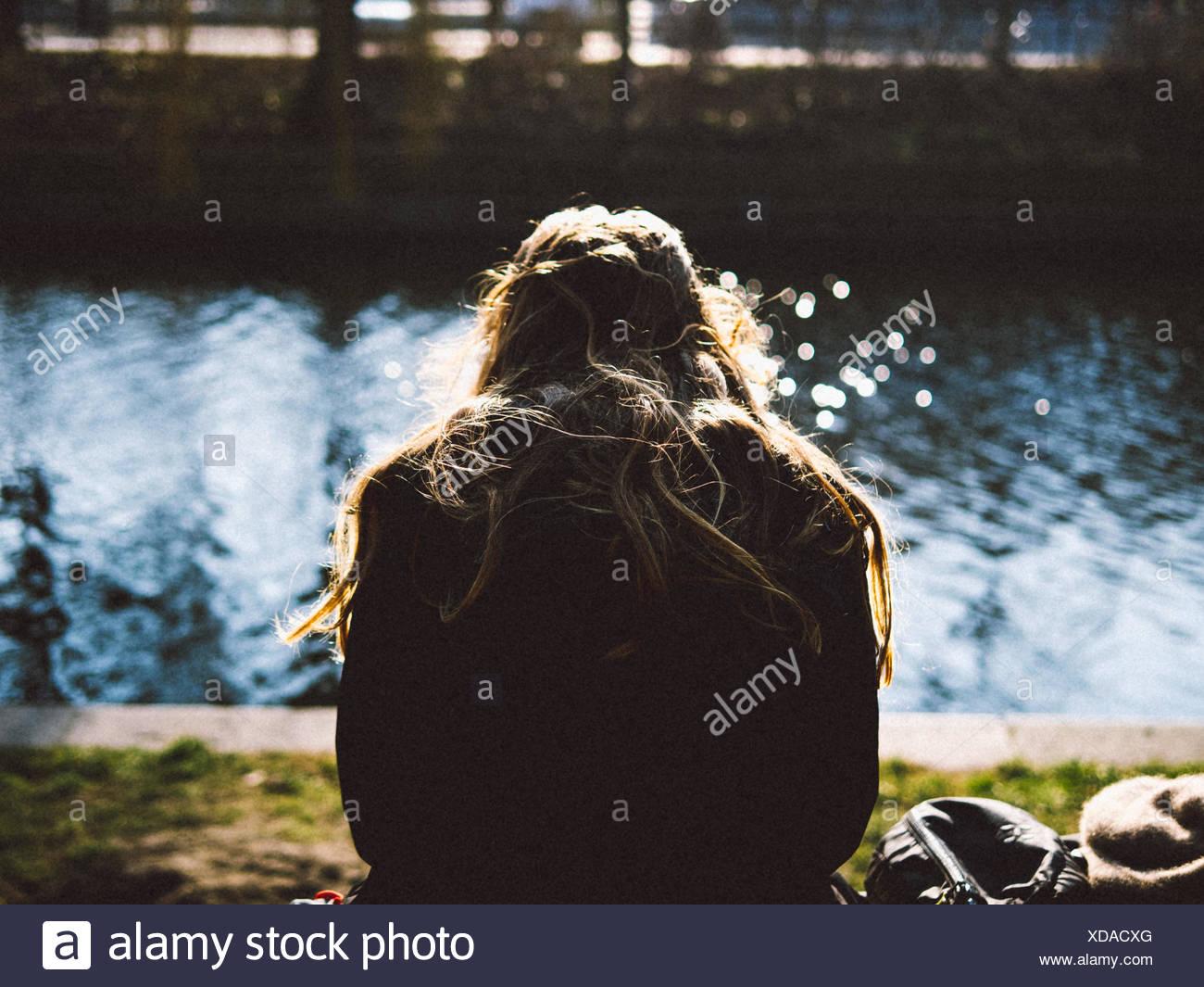 Vista trasera de la mujer relajante en Riverbank Imagen De Stock