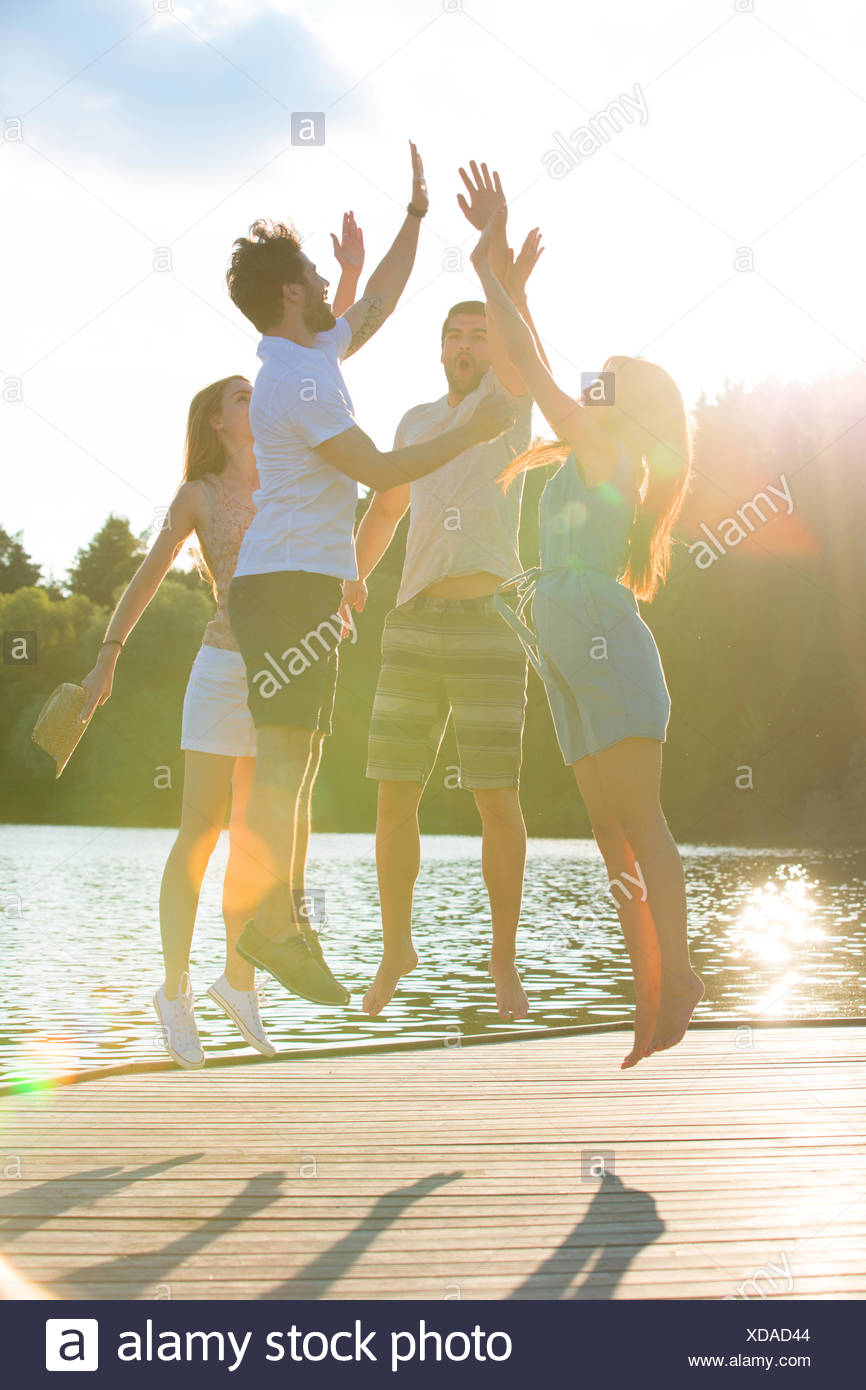 Cuatro amigos alta fiving en un lago de retroiluminación Imagen De Stock